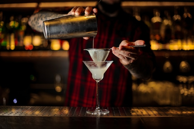 Barista che versa una bevanda gustosa fresca e acida in un bicchiere da cocktail usando lo shaker e il colino
