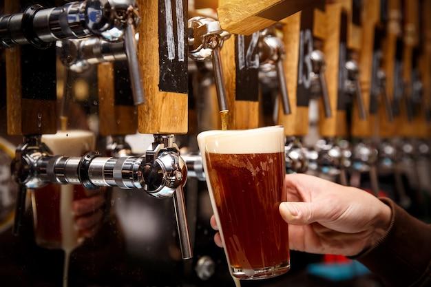 Barista che versa dal rubinetto birra fresca nel bicchiere in pub, bar