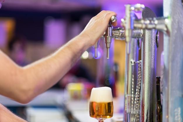 Barista che versa birra chiara in un bicchiere.