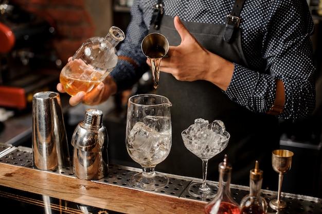 Il barista versa whisky e sciroppo sul ghiaccio nel bicchiere da cocktail