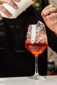 Barista prepara sul bancone aperol spritz un classico rinfrescante aperitivo italiano fatto miscelando