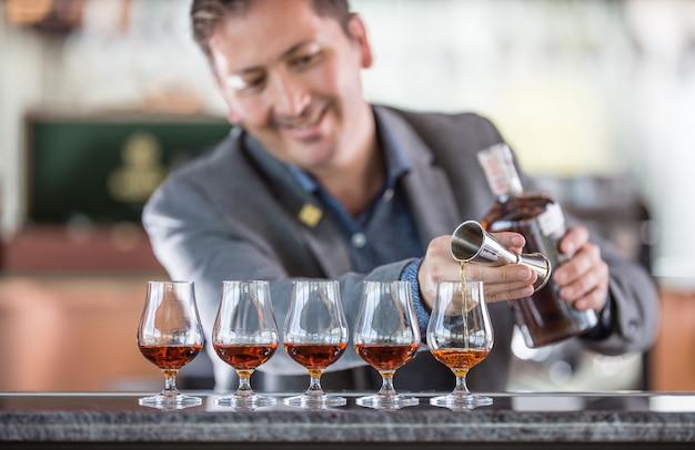 Barista professionista che prepara cinque bevande alcoliche che versa un rum o un cognac di altissima qualità