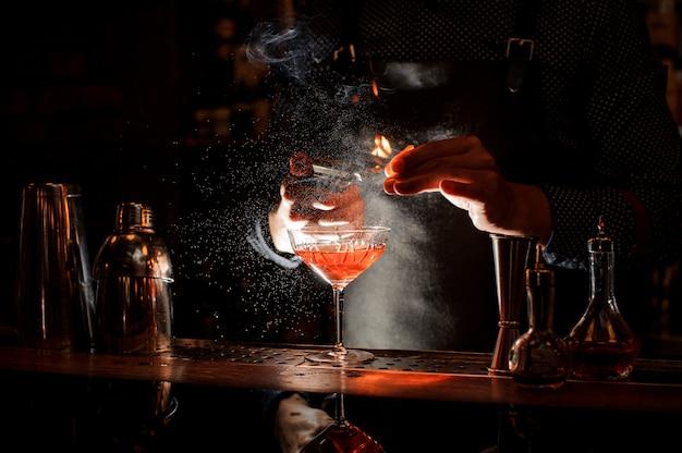 Il barista dà fuoco al dolce cocktail in bocal