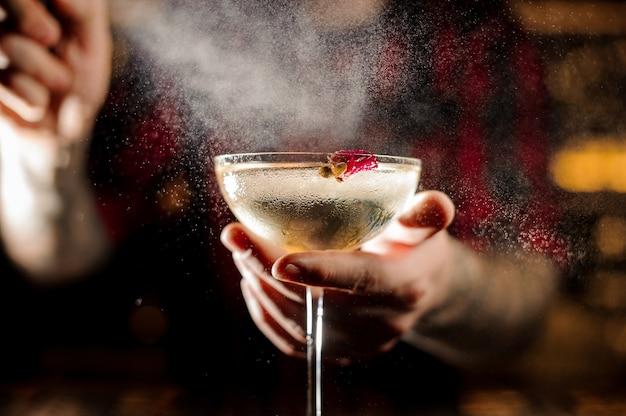 Barista che spruzza amaro sull'elegante bicchiere da cocktail decorato con un piccolo bocciolo di rosa contro le luci