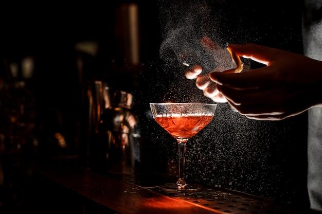 Il barista spruzza una buccia d'arancia nel bicchiere da cocktail
