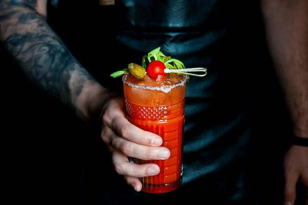 Il barista con la camicia bianca e il grembiule scuro versa una sanguinaria mary nel bicchiere da cocktail sul bancone del bar