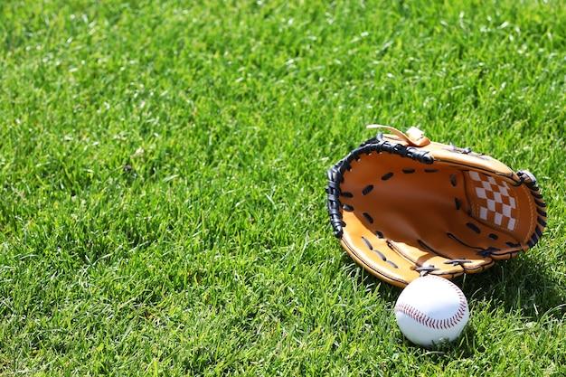 Palla da baseball e guanto sul campo verde Foto Premium