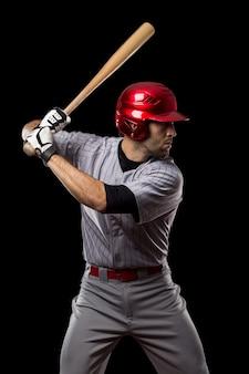 Giocatore di baseball su sfondo nero. studio girato.