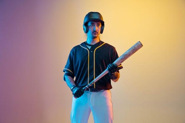 Giocatore di baseball, lanciatore in uniforme nera in posa fiducioso sul muro sfumato in luce al neon. giovane sportivo professionista in azione e movimento. stile di vita sano, sport, concetto di movimento.