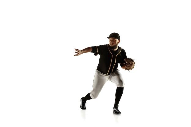 Giocatore di baseball, lanciatore in un'uniforme nera che pratica e si allena isolato su un muro bianco. giovane sportivo professionista in azione e movimento. stile di vita sano, sport, concetto di movimento.