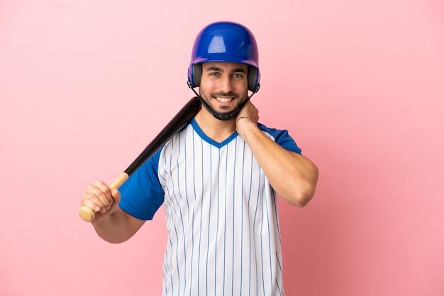 Giocatore di baseball con casco e mazza isolato su sfondo rosa ridendo