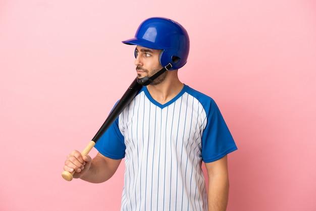 Giocatore di baseball con casco e mazza isolato su sfondo rosa guardando di lato
