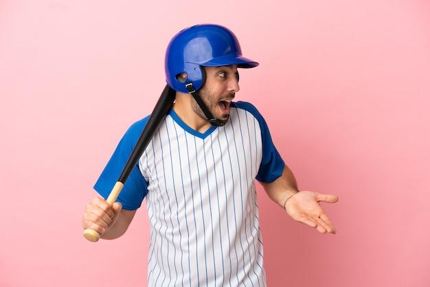 Giocatore di baseball con casco e mazza isolato su sfondo rosa con espressione di sorpresa mentre guarda di lato