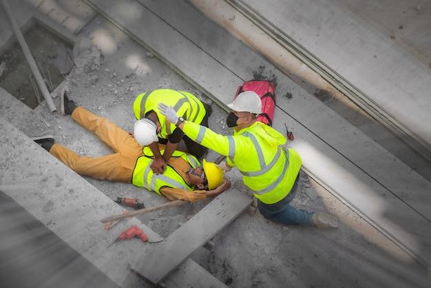 Primo soccorso di base e rcp per incidenti di emergenza nei cantieri. operaio edile è stato ferito in una caduta dall'alto in cantiere. il team di sicurezza e gli ingegneri aiutano a eseguire il primo soccorso