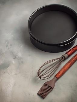 Utensili da cucina di base con stampi torta su sfondo grigio pietra con spazio per il testo.
