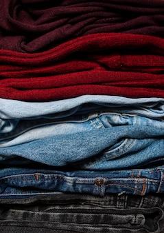 Un guardaroba di base, guardaroba di vestiti. jeans e camicette piegati uno contro uno in primo piano di colori bordeaux, stagione autunno-primavera.