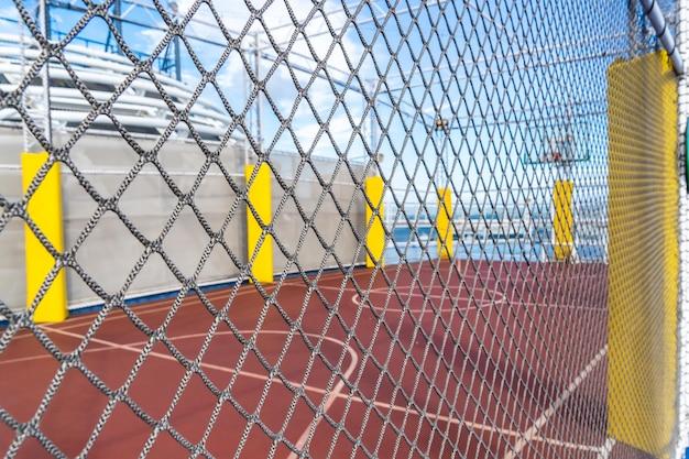 Campo da basket con protezione del filo di maglia per il concetto di sport sportivo di città di strada