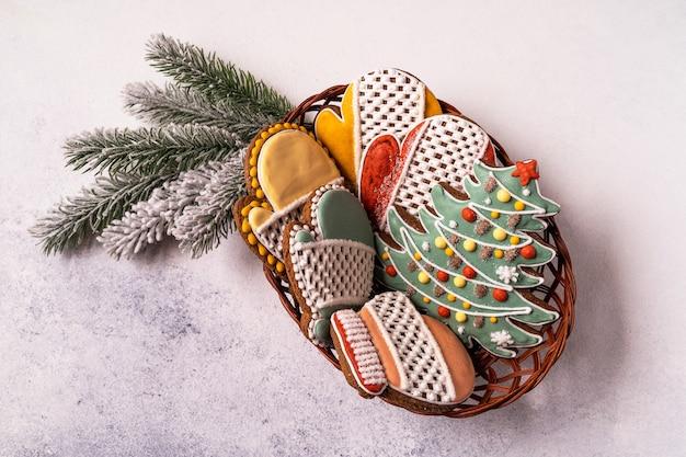 Un cesto di panpepato di natale su sfondo grigio. fiocco di neve, abete, guanto, abete rosso, stella, slitta, coni, cono, stella, campana.