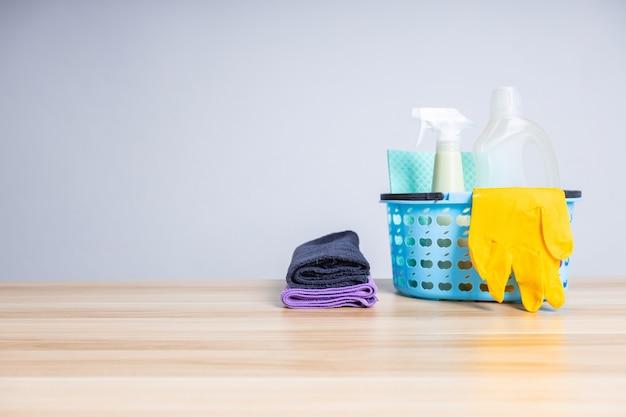 Cesto di prodotti per la pulizia su tavola di legno, servizi di pulizia e concetto di protezione del coronavirus