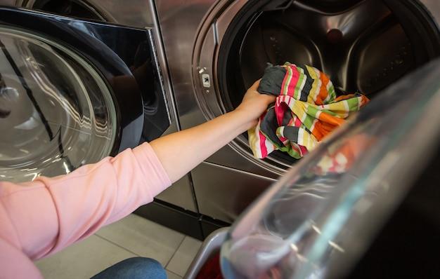 Cesto di panni sporchi nella lavanderia con una specie di lavatrici, lavatrici