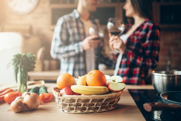 Cesto di frutta fresca sul tavolo, coppia di innamorati che beve vino in cucina a casa, cena romantica in famiglia