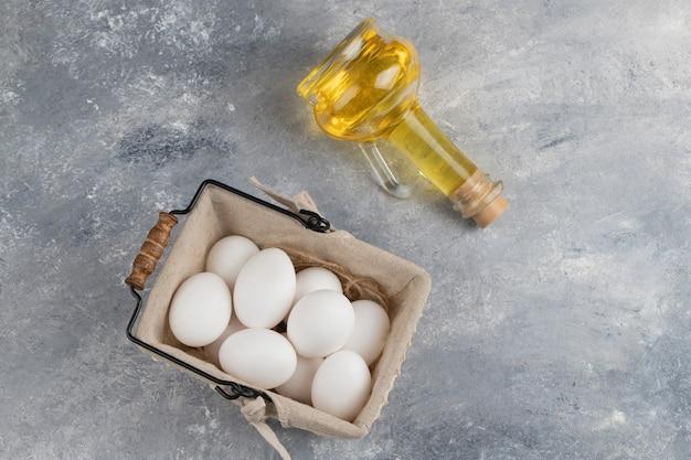 Cesto pieno di uova di gallina bianche fresche con una bottiglia di vetro di olio su una biglia.