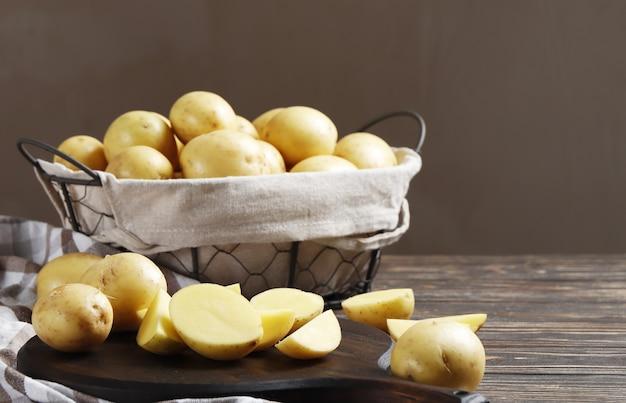 Cesto pieno di patate fresche, tavola, asciugamano e coltello su sfondo di legno, vista dall'alto
