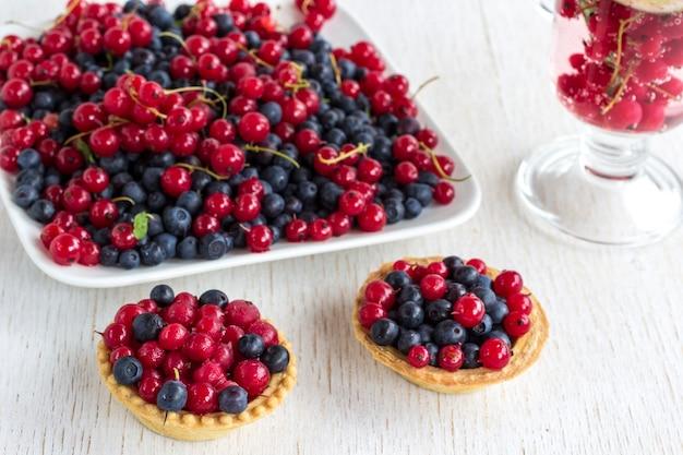 Biscotti a forma di cestino e piatto con ribes rosso e bacche di mirtilli
