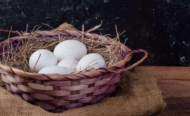 Cesto di uova di gallina bianca con fieno su un tavolo rustico