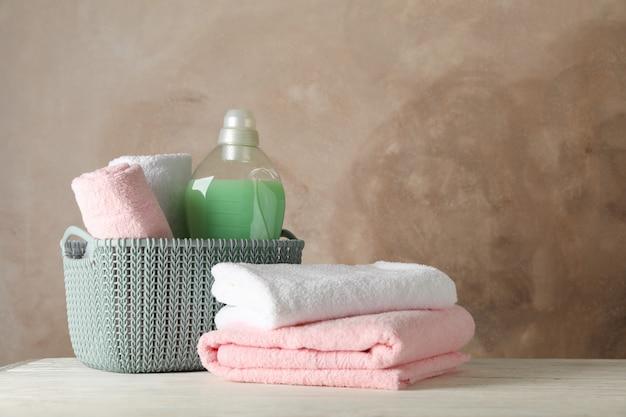 Cesto con asciugamani puliti e liquido per bucato su legno,