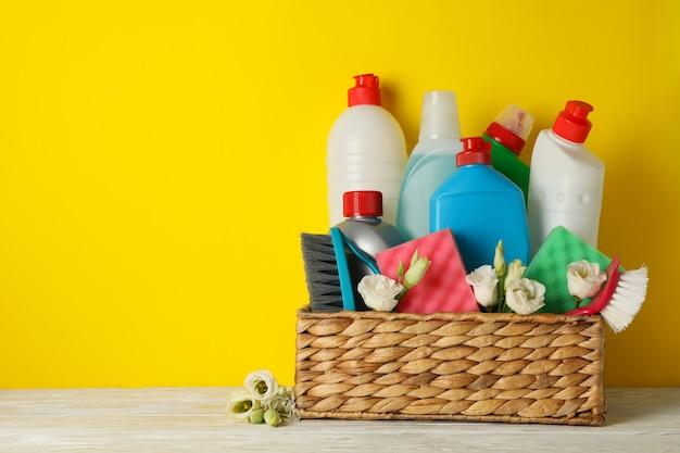 Cestino con strumenti per la pulizia e fiori su sfondo giallo