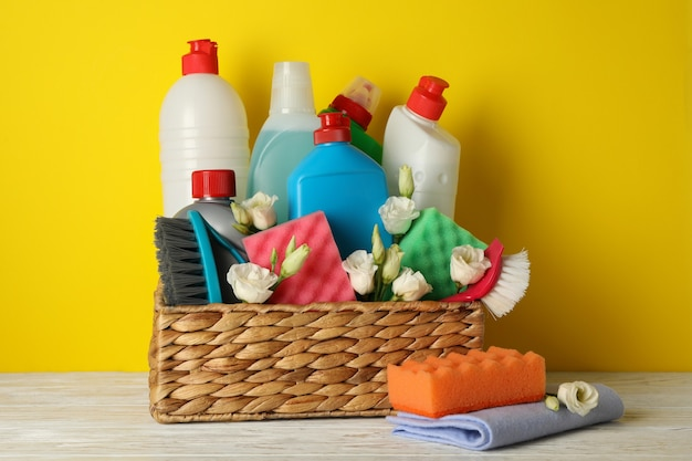 Cestino con strumenti per la pulizia e fiori su colore giallo