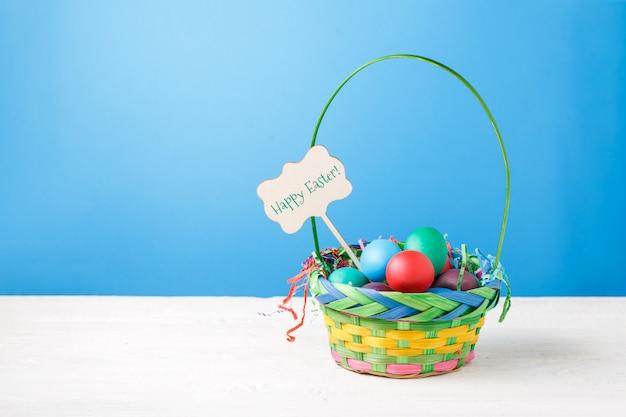 Cestino con uova colorate con augurio di buona pasqua