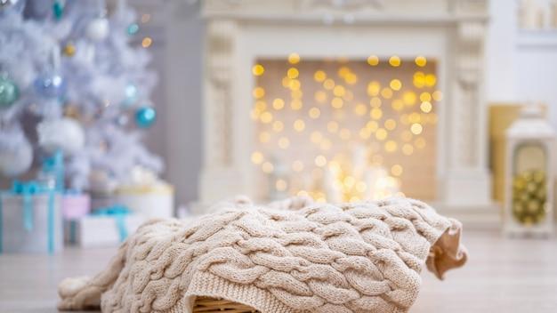 Cestino con una coperta lavorata a maglia nella stanza addobbata per natale