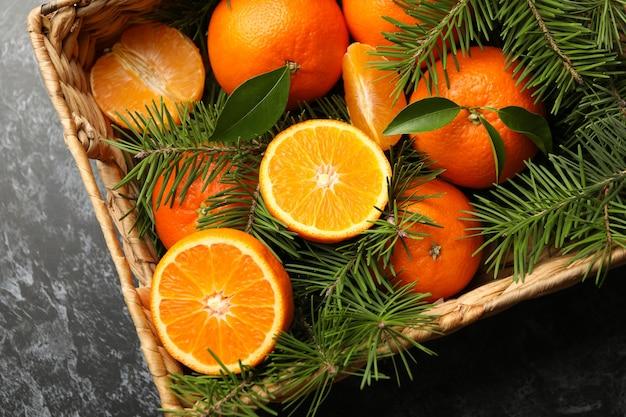 Cesto con mandarini e rami di pino