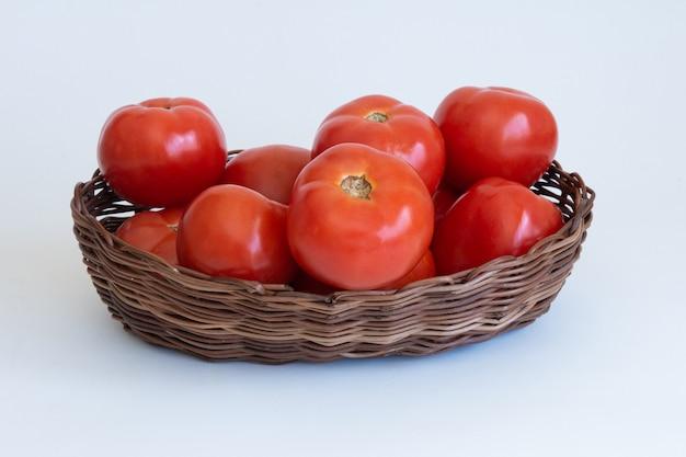 Cestino con pomodori rossi isolati. tracciato di ritaglio.