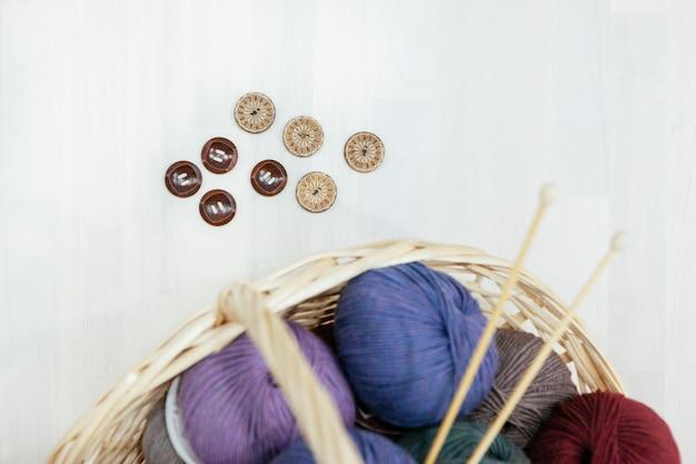 Cesto con una varietà di legno di filati, ferri da maglia e bottoni