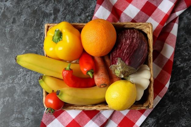 Cesto con frutta e verdura su carta da cucina su tavolo nero smokey