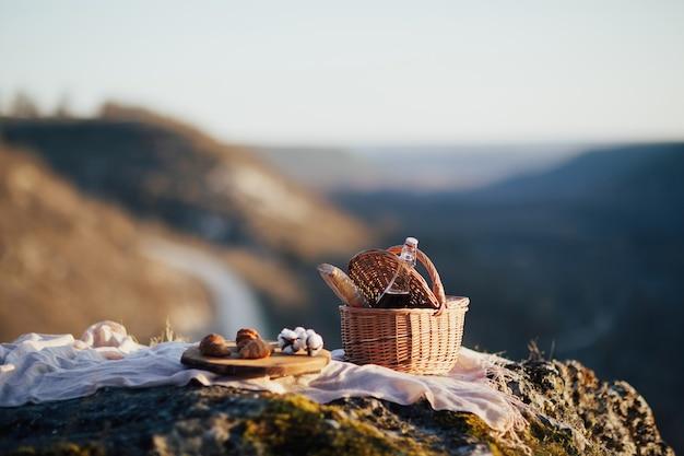 Cesto con vino e baguette e vassoio in legno con croissant