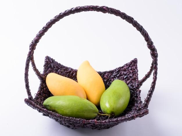 Cesto di manghi gialli e verdi isolati