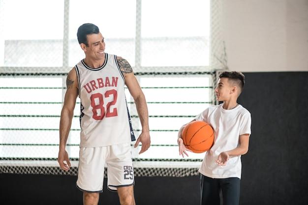 Pallacanestro. allenatore in abiti sportivi bianchi che insegna al ragazzo che gioca a basket