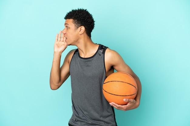 Giocatore di basket afroamericano isolato su sfondo blu che grida con la bocca spalancata di lato