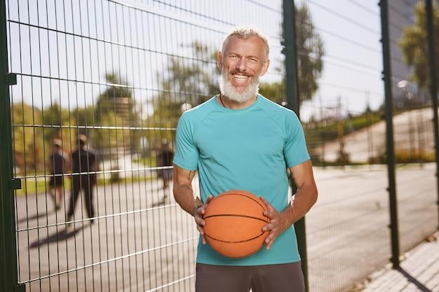 Giocatore di basket uomo maturo felice in abiti sportivi che tiene la palla da basket e sorride alla telecamera