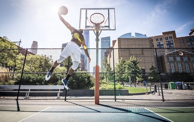 Giocatore di pallacanestro che fa enorme schiacciata