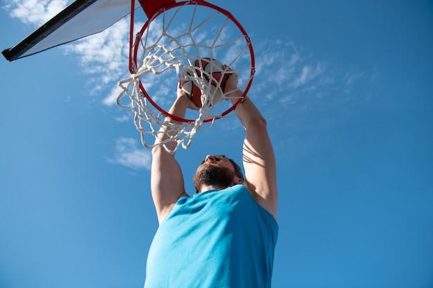 Giocatore di basket che fa un tiro in sospensione sullo sfondo del cielo blu