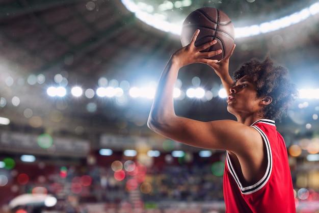 Il giocatore di pallacanestro lancia la palla nel canestro nello stadio pieno di spettatori.