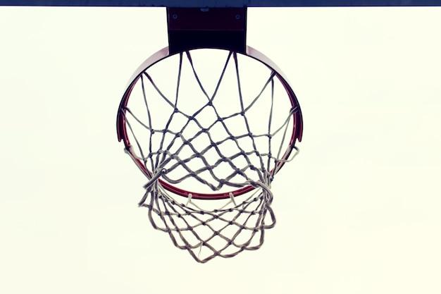Orlo netto di attività all'aperto di sport di pallacanestro su superficie bianca