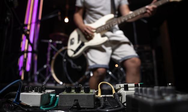 Bassista su un palco con set di pedali per effetti di distorsione.