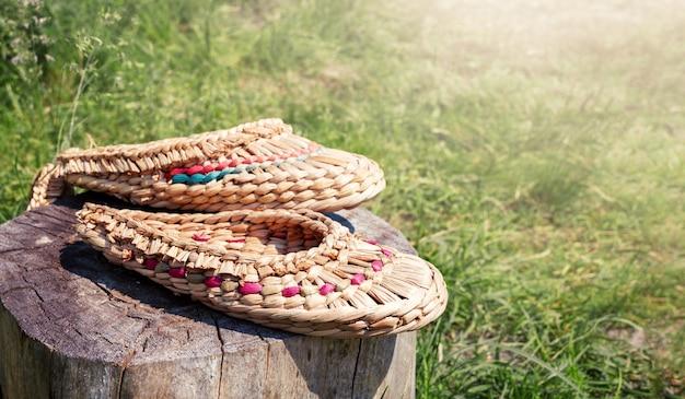Le scarpe di bast intrecciate con materiali naturali giacciono su un ceppo