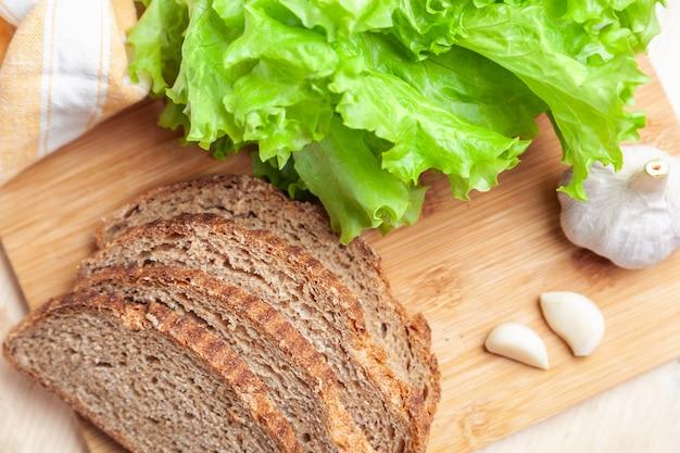 Batavvia foglie di insalata verde e fette di pane su bianco